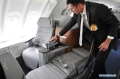 A staff member of Deutsche Lufthansa AG demonstrates the foldable business class seat of the new 747-8 Intercontinental in Everett, the United States, May 1, 2012. Deutsche Lufthansa AG is the first commercial airline to deploy the new 747-8 Intercontinental. (Xinhua/Zhang Zhiyu)