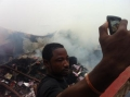 A man uses a cellphone to photograph himself in front of the wreckage of the passenger plane.