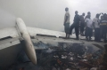 People stand on a wing of the wrecked plane. The plane crashed in a densely populated neighborhood near the airport. A spokesman for Nigeria's national emergency management agency said there were likely more casualties on the ground, but the number was unknown.