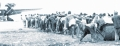 1922年,修建飞机场民工用麻绳拴住石碾子,喊着号子,依靠人力拉着石碾子来挤压,平整土地。