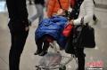 1月5日凌晨,大量旅客仍滞留昆明长水国际机场。昆明长水国际机场1月3日受大雾天气影响,取消440个航班,机场滞留约7500名旅客。从4日早开始,截止5日凌晨3时30分,长水机场共起降航班702架次。图为一名小女孩盖着父亲的衣服睡在行李推车上。 (摄影:刘冉阳)