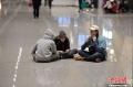 1月5日凌晨,大量旅客仍滞留昆明长水国际机场。昆明长水国际机场1月3日受大雾天气影响,取消440个航班,机场滞留约7500名旅客。从4日早开始,截止5日凌晨3时30分,长水机场共起降航班702架次。图为在机场席地而坐的旅客。 (摄影:刘冉阳)