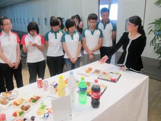 工作人员向小学员介绍港龙航空商务舱及经济舱的餐膳。