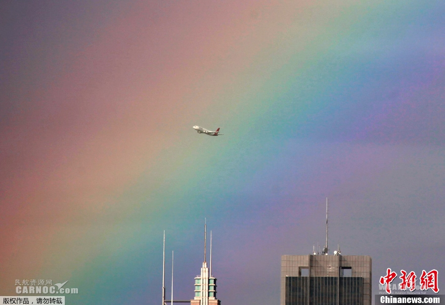 当地时间2013年6月17日,澳大利亚悉尼上空现一道彩虹,飞机从中