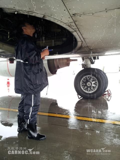 7月13日,青岛机场大雨,机务人雨中全力保障.东航山东机务检查起落架舱