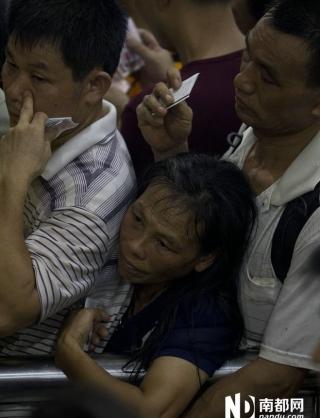 8月17日下午,大批持票无法进站的旅客挤爆广州火车站售票大厅,一名女等待退票的女乘客挤在人群中。