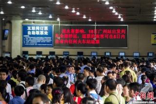 8月18日,广州火车站的售票大厅临时改为退票大厅,正在为旅客办理退票相关业务。当日,广州站售票厅开放45个退票窗口,进站口改为退票口。受粤北地区持续暴雨引发山体垮塌和泥石流影响,京广线上下行线于17日晚中断行车。自18日零时起,广州火车站往各个方向的列车全部停运。广铁集团估计,超过8万余旅客出行受到影响。 (摄影:龙宇阳)