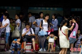 8月18日,广州火车站的售票大厅临时改为退票大厅,为旅客办理退票相关业务,部分旅客留在火车站广场附近等候进一步的消息。受粤北地区持续暴雨引发山体垮塌和泥石流影响,京广线上下行线于17日晚中断行车。自18日零时起,广州火车站往各个方向的列车全部停运。广铁集团估计,超过8万余旅客出行受到影响。 (摄影:龙宇阳)