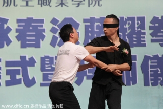 Tu Tengyao performs self-defense tactics while wearing an an eye mask during the demonstration. [Photo/IC]