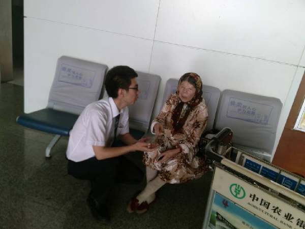 茹.���nz#.{S�;��#��_图:艾力扎提用维语安慰误机的阿奶奶 摄影:茹沙依