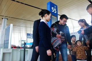 """""""徒弟""""王早艳去年刚大学毕业,面对第一次的春运保障,今年她将在春运路上边学边练,带着憧憬和向往,为了自己的第一个春运而努力。图为王早艳对儿童旅客的特殊关照"""