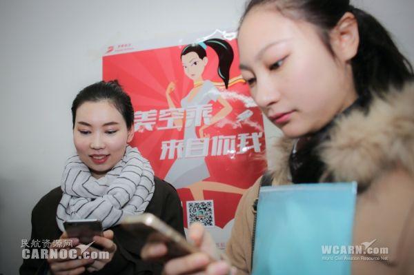 在招聘海报前,用手机报名填写资料的考生学员