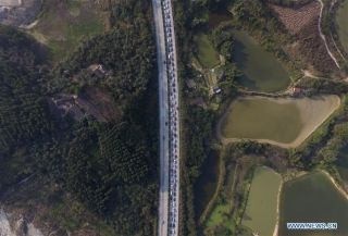An aerial photo taken on Feb. 12, 2016 shows vehicles moving slowly on an expressway near Nanning, south China's Guangxi Zhuang Autonomous Region. Highways and railroads across China have seen increasing passenger flow while millions of Chinese return to work as the week-long Spring Festival holiday comes to an end. (Xinhua/Huang Xiaobang)