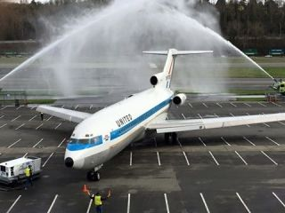 The first Boeing 727 is given a water cannon salute at Seattle's Museum of Flight after completing its final flight on March 2, 2016.