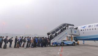 旅客在大雾中登机。 (摄影:贺晟)