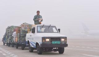 货运装卸工在大雾中运送货物。 (摄影:贺晟)