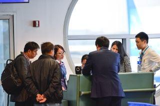 乘机员在登机口耐心解释航班延误原因。 (摄影:贺晟)
