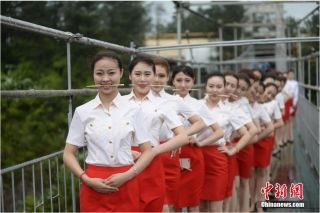A group of flight attendants went through etiquette training courses on a 180-meter-high terrifying glass-bottomed bridge in Shiniuzhai National Geological Park. Photo: Chinanews.com