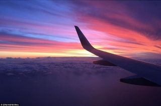 A passenger captures the sunset and clouds with tinges of pink and purple that almost look like cotton-candy.