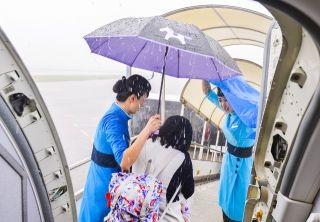 """5月29日下午14点30分,厦航MF8218航班在厦门机场落地后正准备下客,突然暴雨倾盆,大雨浇得人几乎睁不开眼睛,几秒钟就淋透透。航班乘务长带着乘务员想方设法让旅客少淋雨,特别是老年旅客和怀抱幼儿的家长。她们找出自己的伞,没伞的干脆举着干净的大垃圾袋披挂上阵。她们撑着一把小伞站在客梯车上给旅客遮着雨,提着行李,口中还不停地提醒""""雨天湿滑小心滑倒""""。等把旅客一一送上摆渡车,她们自己已经浑身湿透。真心是最好的服务,虽然漂亮的妆容残了,但暴雨中的身影更突显了她们内在的美,旅客们纷纷拿手记录当时的场面。"""