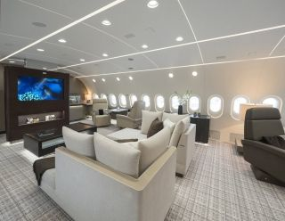 Looking toward the front of the plane, the lounge features a pair of day beds positioned in front of a large 55-inch flat-screen display. On each side of the center screen, there are individual seats each equipped with a 24-inch screen. Kestrel Aviation Management
