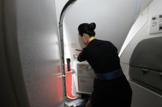 A flight attendand closed the cabin door. Photograph by Wan Quan/China Pictorial