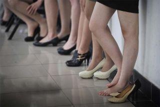 长时间的等待让穿着高跟鞋的姑娘不堪负重。