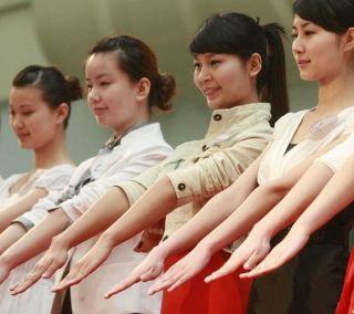 姑娘们伸出双手尽量展示出自己最美好的一面。