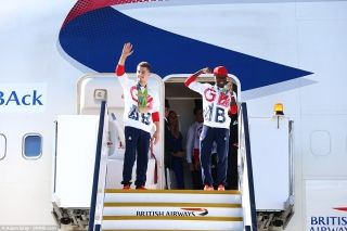 Gold winners: Gymnast Max Whitlock (left) and boxer Nicola Adams (right), who both won their respective competitions in Brazil, smile and wave as Team GB's medal winning athletes return to Britain from Rio on a British Airways flight.