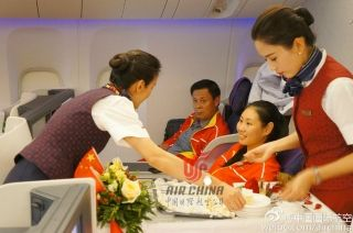 Air China flight attendants serve Olympic stars on board flight CA604. Photo by Air China