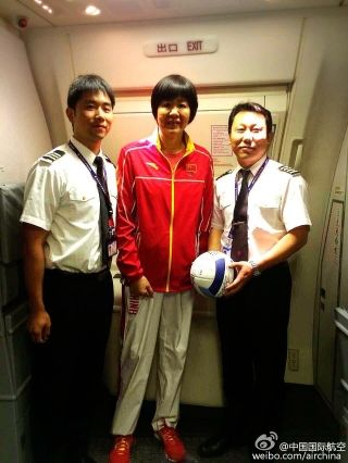 Air China flight attendants serve Olympic stars on board flight CA604. Photo by Air China