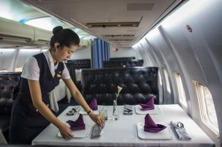 A waitress puts finishing touches on a table inside China's first airplane restaurant. Wang He/Getty Images