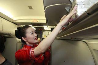 10月1日7时12分,川航空乘协助旅客安放行李 (摄影:高昂)
