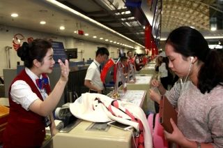 10月1日早6时50分,川航地服工作人员为早班旅客办理乘机手续 (摄影:高昂)