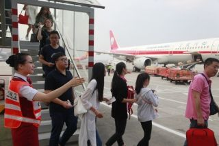 10月1日7时24分,川航地服工作人员引导旅客搭乘摆渡车 (摄影:高昂)