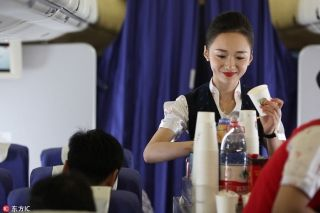 Liu Miaomiao serves lunch for the passengers onboard the plane bound for Beijing. [Photo/IC]
