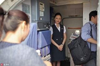 Liu Miaomiao welcomes the passengers boarding the flight bound for Beijing in Shenzhen city, South China's Guangdong province. [Photo/IC]