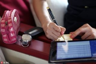 Liu Miaomiao writes down passengers' special dietary requirements. [Photo/IC]