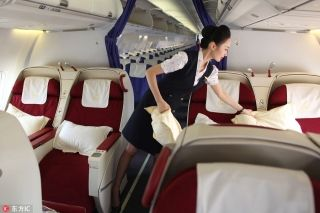 Liu Miaomiao prepares the first-class cabin onboard the plane bound for Beijing. [Photo/IC]