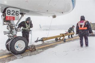 飞机推到远机位,机务人员把牵引杠歇下 (摄影:陈松)