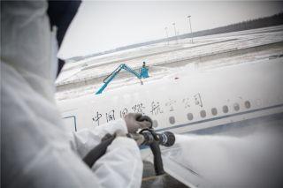 除冰车上很高的地方,除冰员为飞机机身除冰雪 (摄影:陈松)