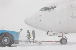 拖车正在把一架航班拖回机位 (摄影:陈松)
