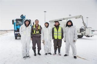 机务除冰员在两台除冰车下 (摄影:陈松)