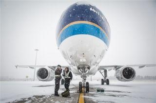 两名机务正在飞机下和机长保持联络准备放行航班 (摄影:陈松)