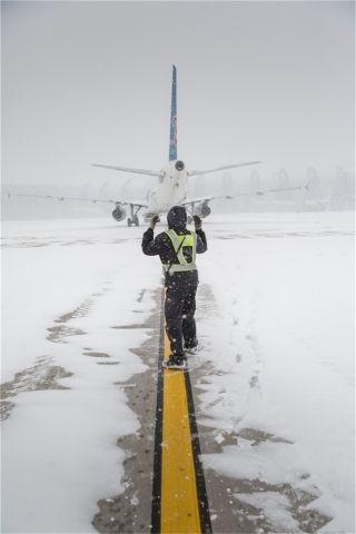 一名机务正引导一架刚刚登机完毕的飞机划向远机位 (摄影:陈松)