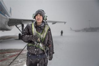 一名机务跟随推出的航班,带着耳麦对讲和驾驶员时刻保持联络 (摄影:陈松)