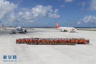 1月6日,两架民航客机降落南沙永暑礁新建机场。这是相关人员合影留念。当日,中国政府征用的两架民航客机先后从海口美兰机场起飞,经过近2小时的飞行于10时21分、10时46分平稳降落南沙永暑礁新建机场并于当日下午返回海口,试飞成功。永暑礁新建机场位于我国南沙永暑礁上,是我国目前最南端的一座机场。 新华社记者 邢广利摄