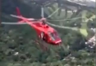 巴西救援直升机贴地悬停接人 螺旋桨成割草机