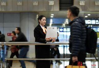 """21岁的宫晓培是一名专车接机员。短短一年多时间,她从一个懵懂的职场""""菜鸟"""",变身专业的接机员领队。因为服务好、笑容亲切,她被同事和客户称为""""最美接机员""""。(来自:腾讯图片) (摄影:张伟)"""
