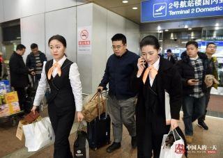 晓培和刘帅帅接过乘客的行李,一路将乘客带到专车停放处。她说,接机员最多时要接30多单,每天来回接送乘客要走十多公里。 (来自:腾讯图片) (摄影:张伟)